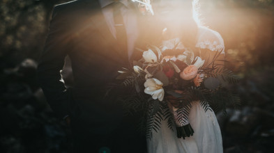 A couple is dressed for a wedding and the bride is holding a bouquet.