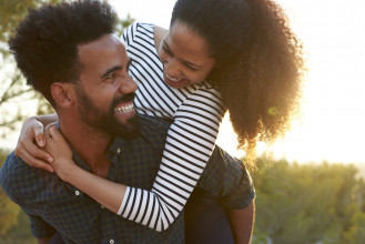 Laughing, young, black couple having fun as he gives her a piggyback ride outside