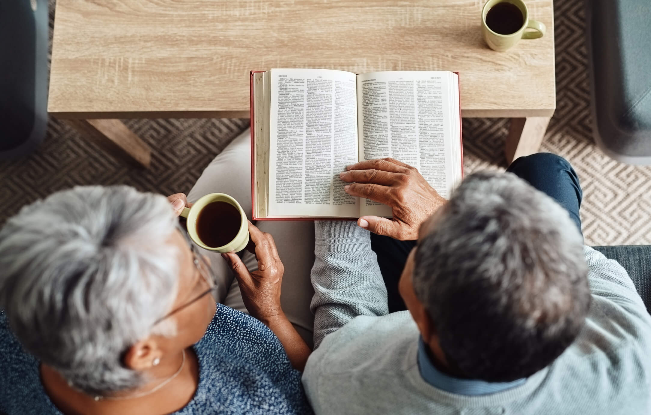Seated elderly couple reading the Bible