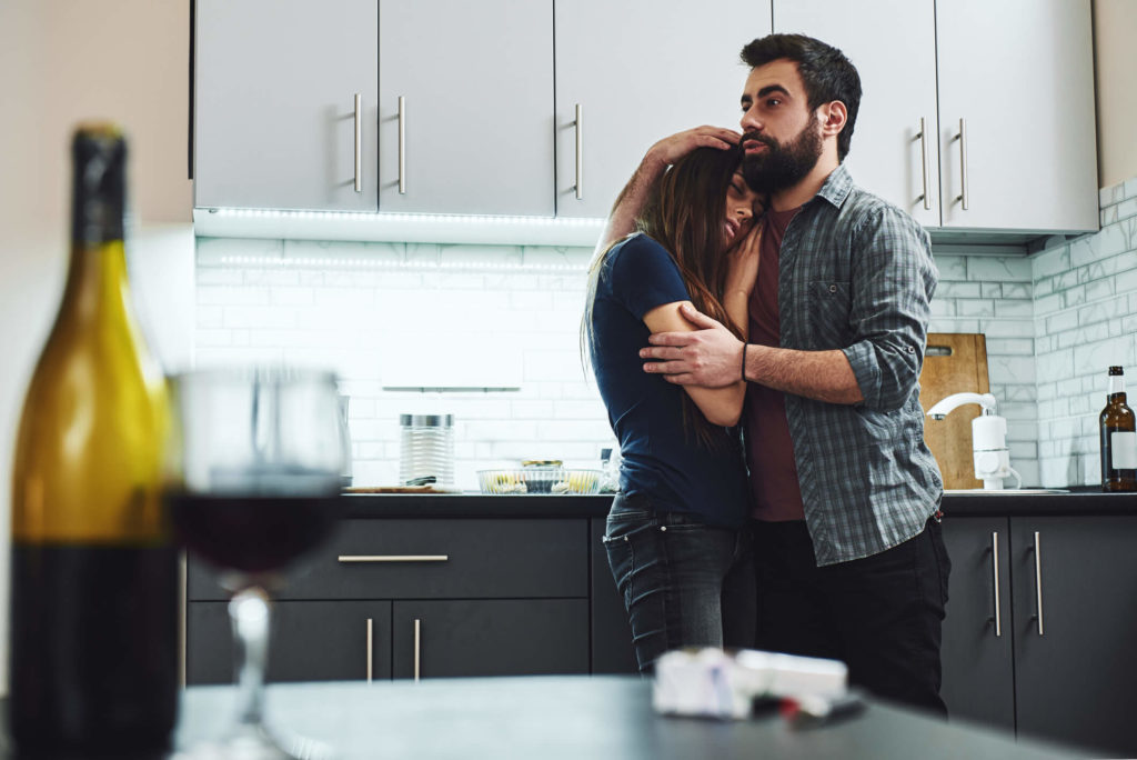 Concerned husband embracing his sad wife in their kitchen, with her head resting on his shoulder