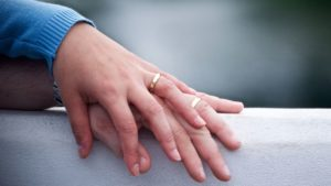 woman's hand resting on man's hand with wedding bands