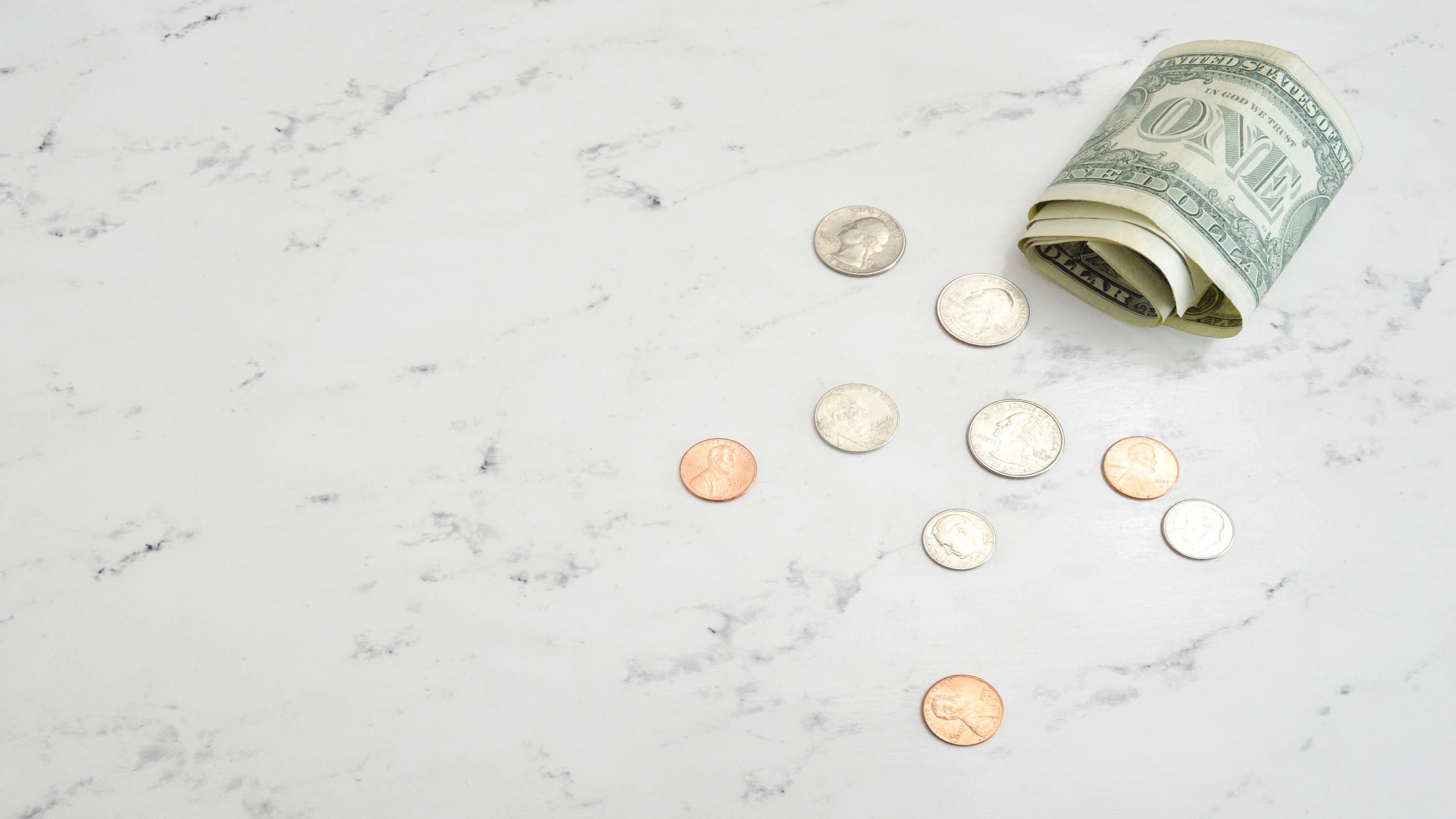 dollar bills with coins on table