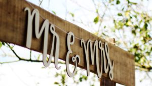 mr and mrs signage on brown board with tree in background
