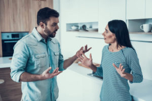 Couple standing in their kitchen having a tense discussion