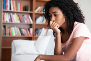 Worried teen girl sitting on a couch staring off camera, contemplating her troubles with her head resting on her hand.