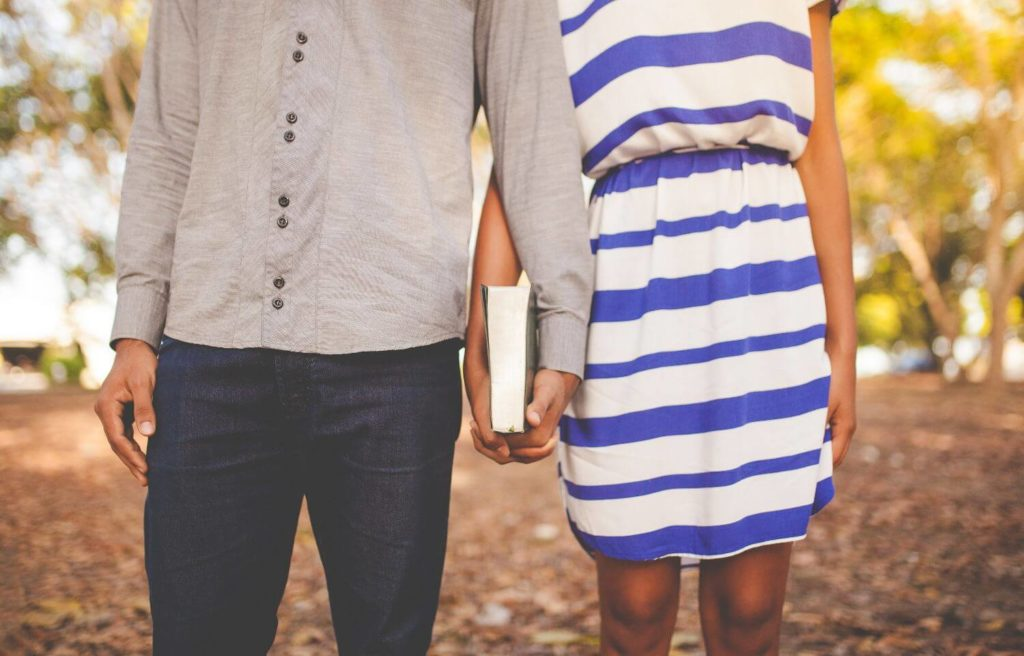 Close up of young couple holding hands which are also holding a Bible together. The couple's heads are not shown.