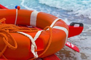 Close up of orange life buoy resting on edge of boat with seashore in background