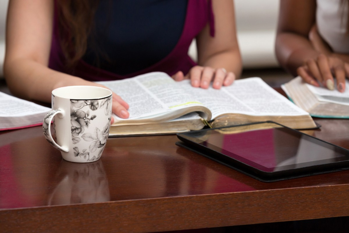 Close up of several open Bibles on a table with women's hands resting on them, indicating a Bible study
