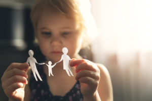 little girl with paper family in hands.