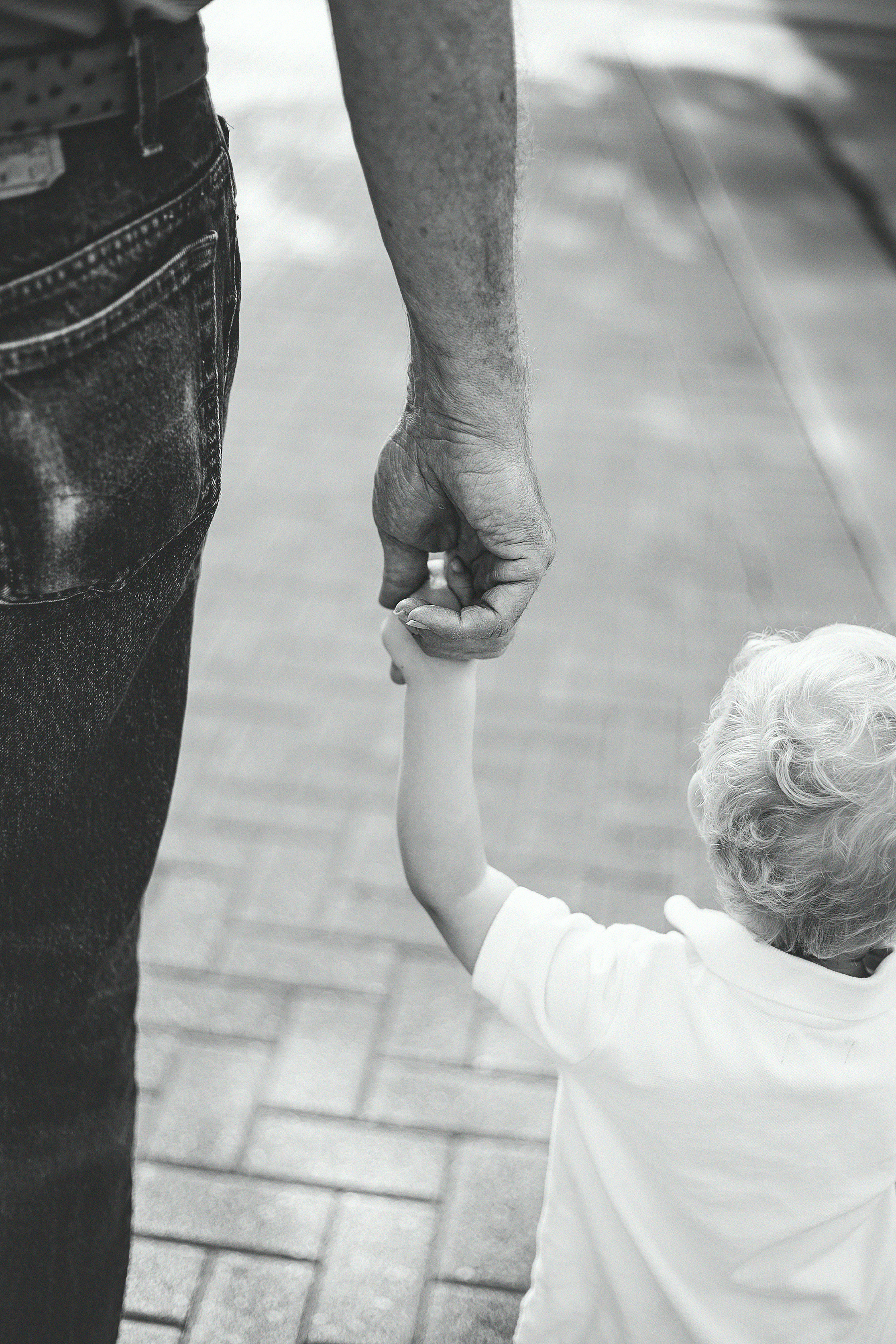 Black and white of a father's hand holding his young son's hand, shown from behind