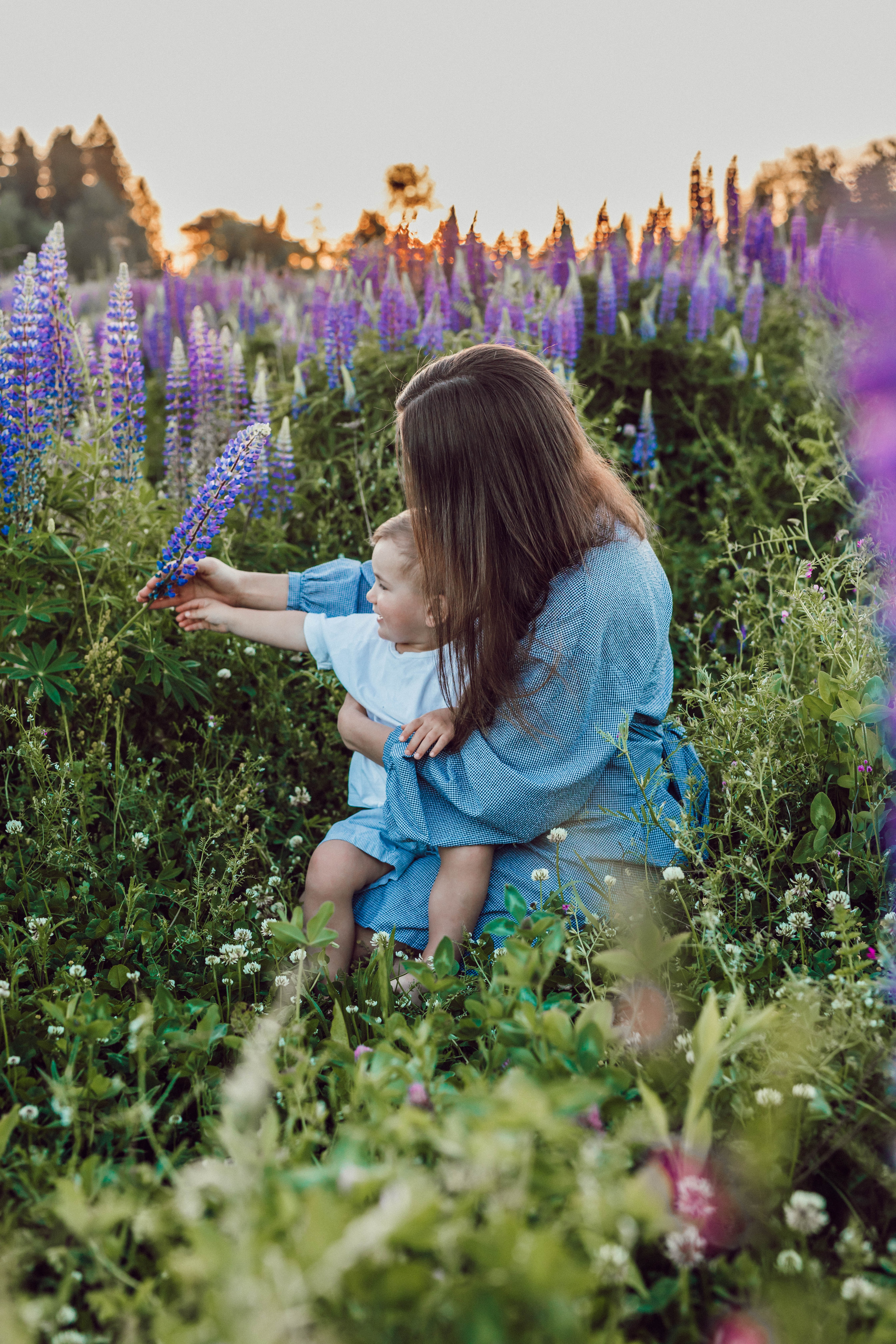 Mom holding young son in field of purple flowers