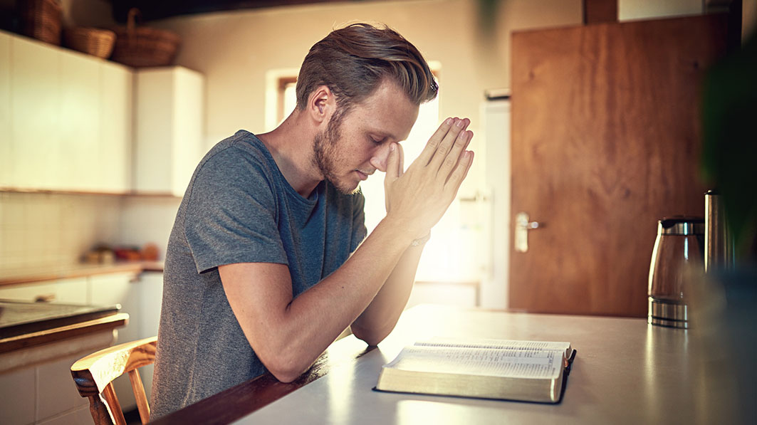 A man seated at a kitchen table praying before an open Bible