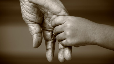 Black and white close-up of a child's hand holding an elderly person's hand