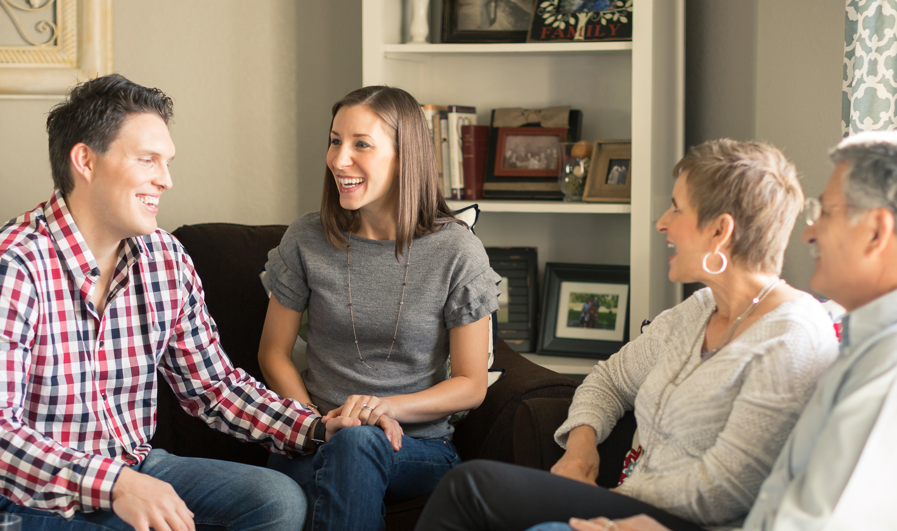 A younger couple sits with an older couple on couches in a living room.