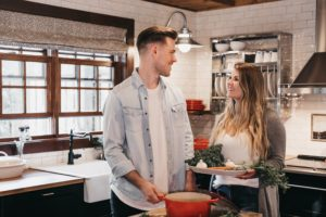 Husband and wife working together in kitchen