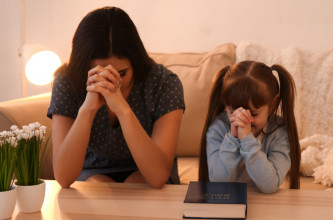 Mom praying with young daughter