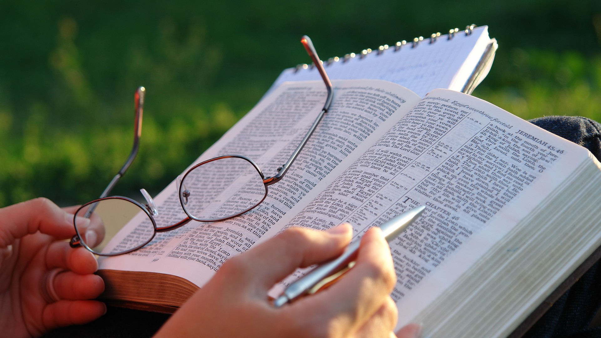Close-up of a woman's hands holding her glasses and studying the Bible