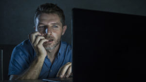 man nervously looking at computer screen