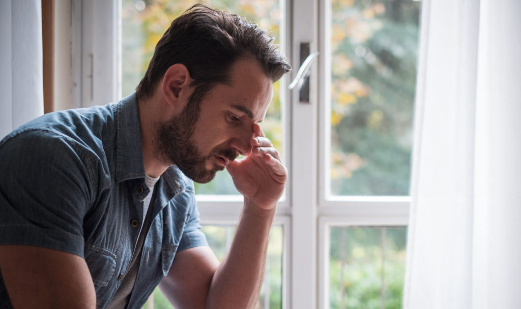 Worried man looking thoughtful out of window