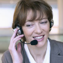 Headshot of a smiling businesswoman taking a call on her headset