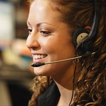 Close up, profile shot of a smiling professional woman taking a phone call on her headset