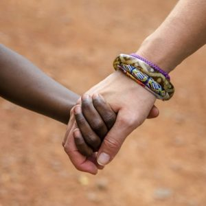 Close up of a white adult's hand holding the smaller hand of a black child