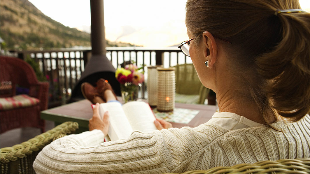 Christian woman practicing self-care by reading a book on a wooden porch