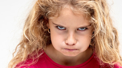 Portrait of preteen girl making an angry face