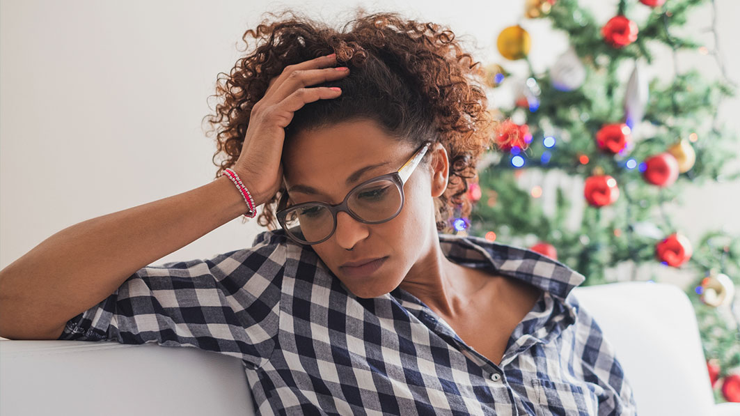 Unhappy-looking African-American woman sitting on her couch, resting her head in her hand; a Christmas tree in the background