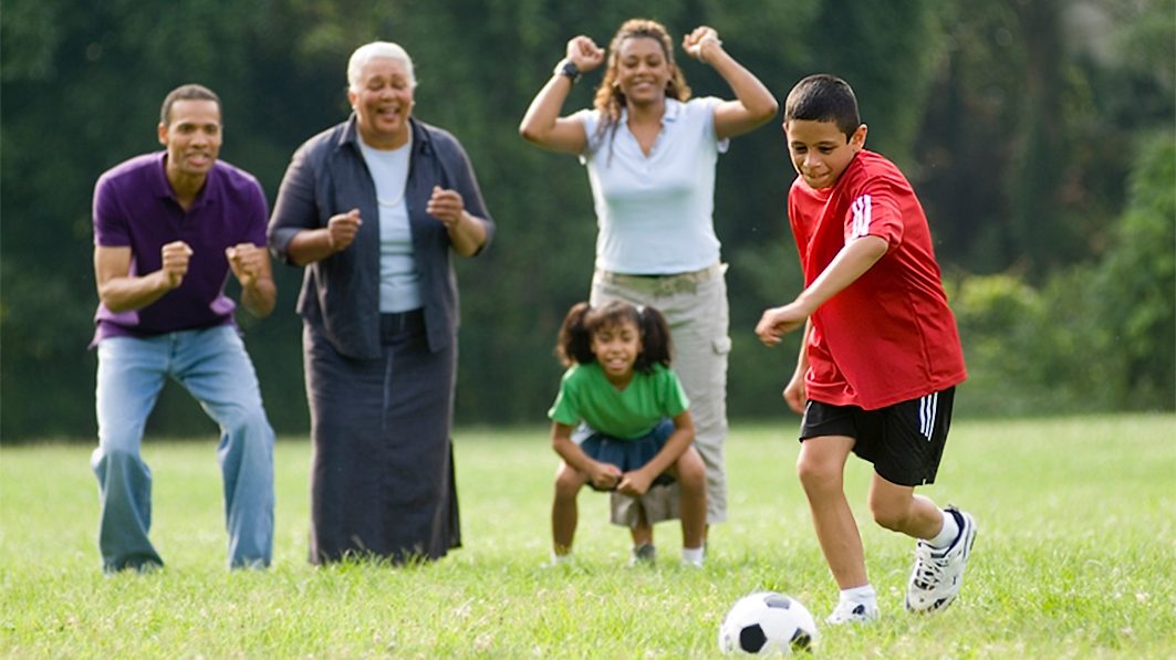 Family looks on as boy plays a soccer game