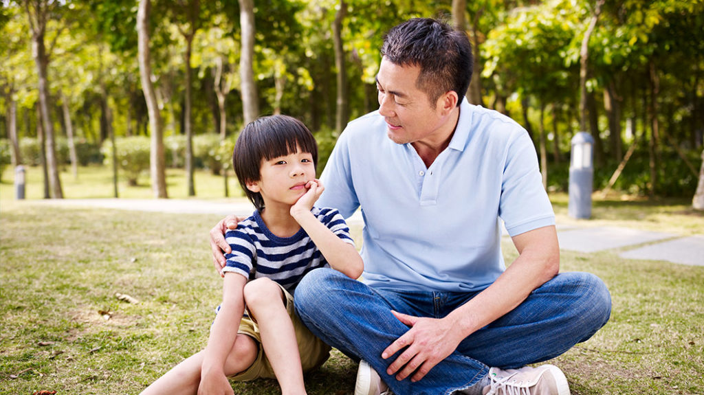 Man and his son sitting in the grass in a park. The father has his arm around his son.