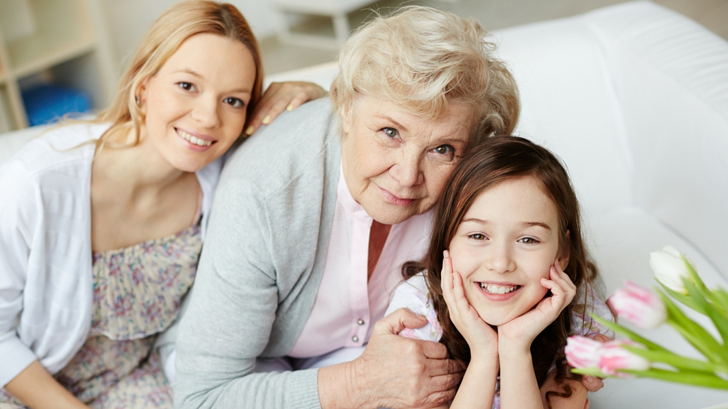 Grandmother smiling beside her two granddaughters.