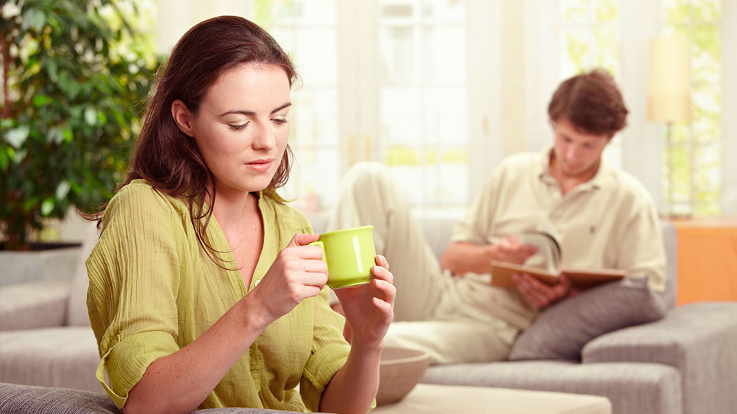 Woman in green holding a coffee cup, with her husband out of focus behind her reading a book