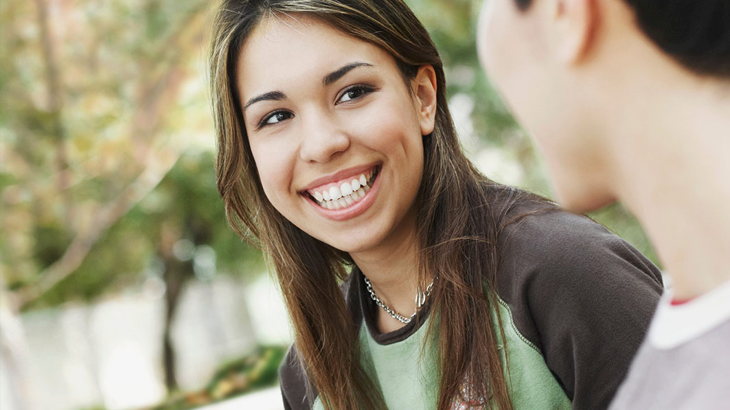 Teen girl smiling at a boy standing beside her