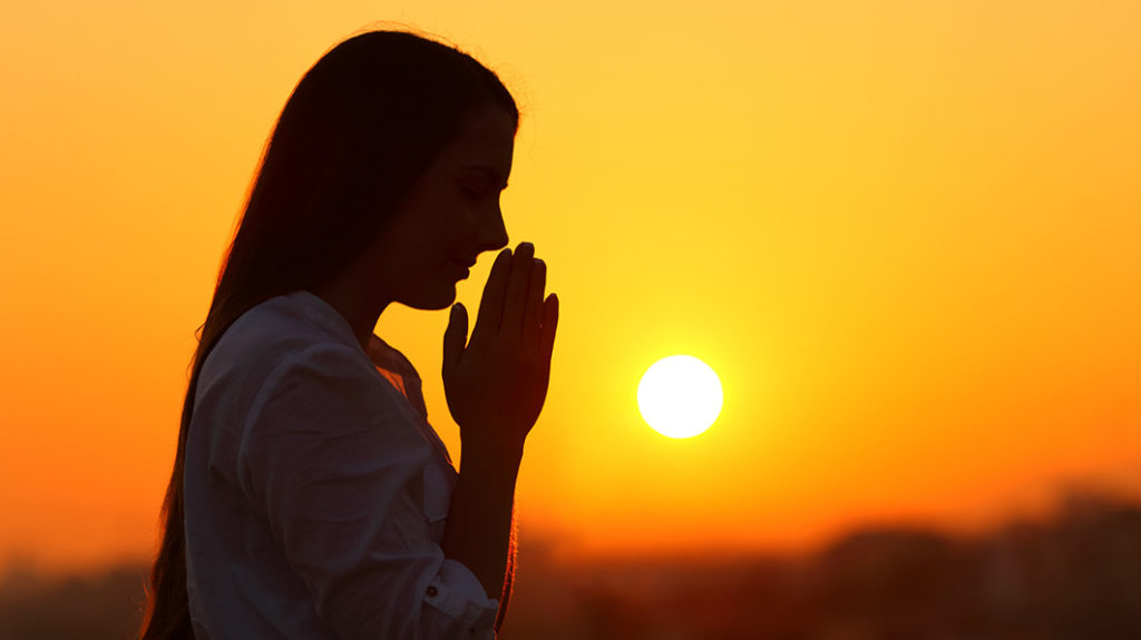 Silhouette of woman praying against backdrop of a sunset