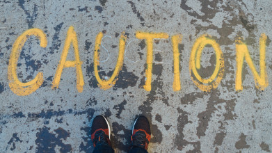 Shown from the perspective of someone looking down, the word 'caution' is spray-painted in large letters on the pavement