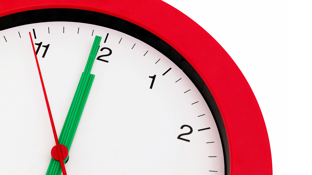 Close up of a circular red clock with a white face, showing the time of about 5 seconds before noon (or midnight)