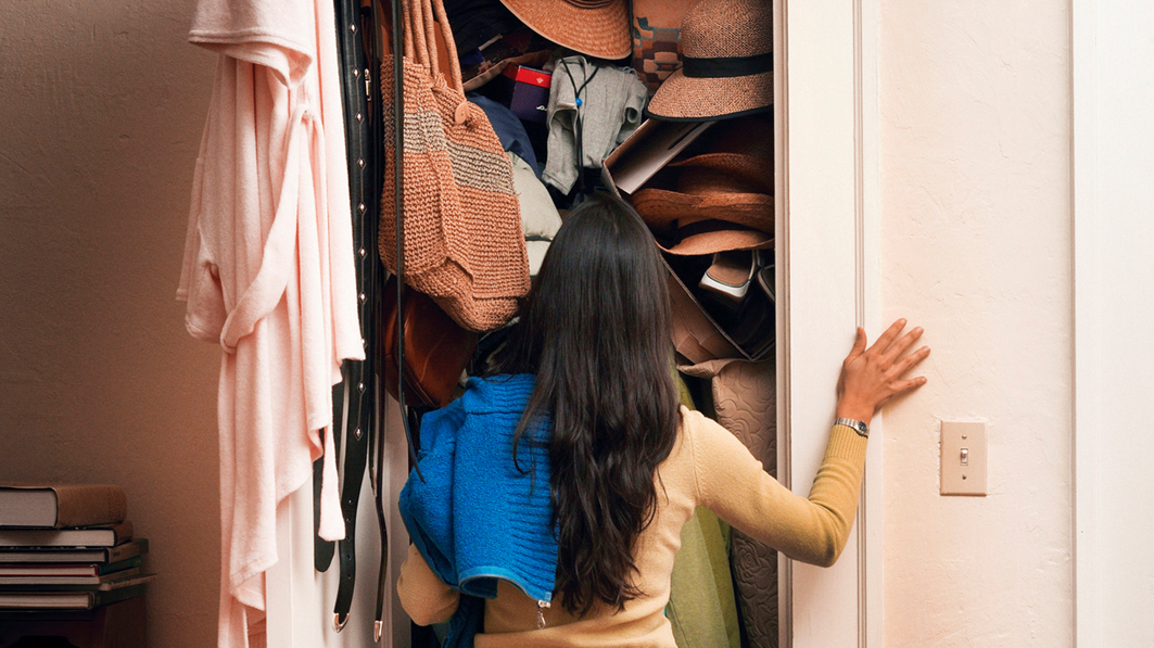 Shown from behind, a dark-haired woman staring into a overstuffed closet