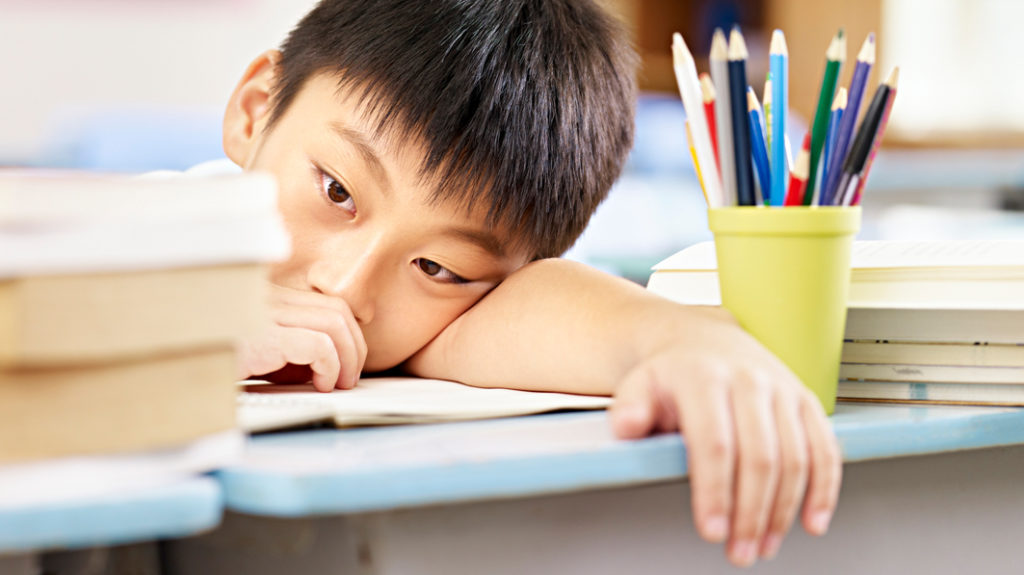Young, serious-looking Asian boy resting his head on his arm on his school desk