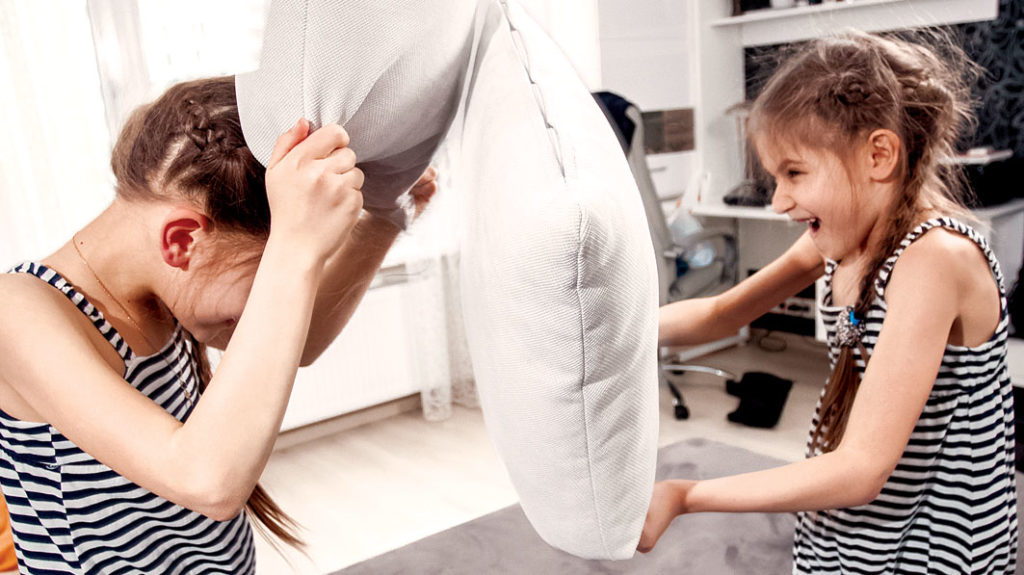 Two young twin girls having a pillow fight