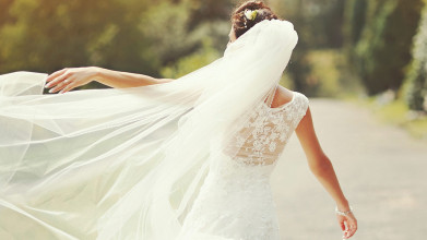 Shown from behind, a bride standing outside, her left arm raised, following the flow of her veil in the breeze
