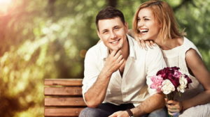 Happy couple sitting on a park bench. He's smiling at the camera, she's laughing, looking to the side and holding a bouquet
