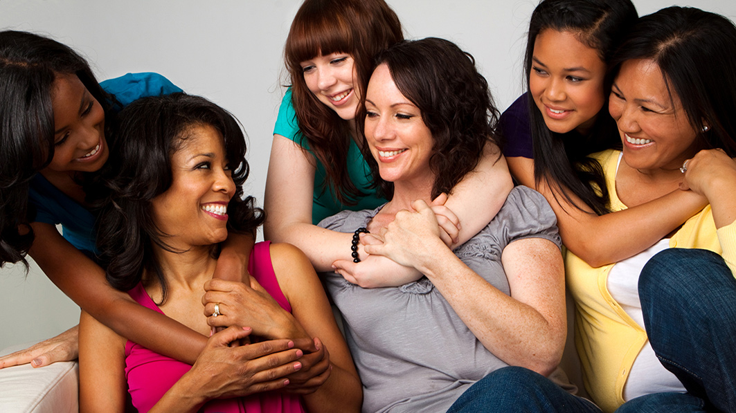 A diverse group of moms and daughters smiling at one another