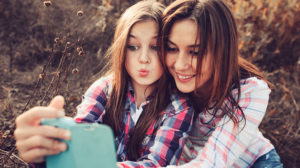 mother and daughter making selfie outdoors