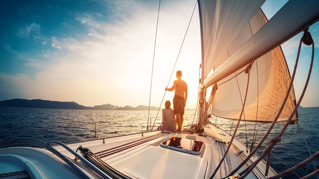 Shown from behind, a couple on the bow of a sailboat looking out over the ocean at a sunrise