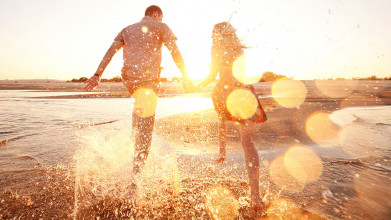 Shown from behind, couple holding hands splashing water as they run along the beach at sunrise