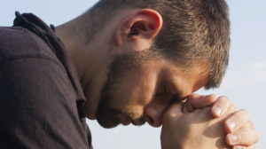 Close-up, profile image of a contrite man with his head bowed, his hands clasped in prayer