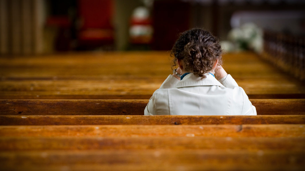 a woman sits silently in church considering weather or not to go to an abortion clinic.