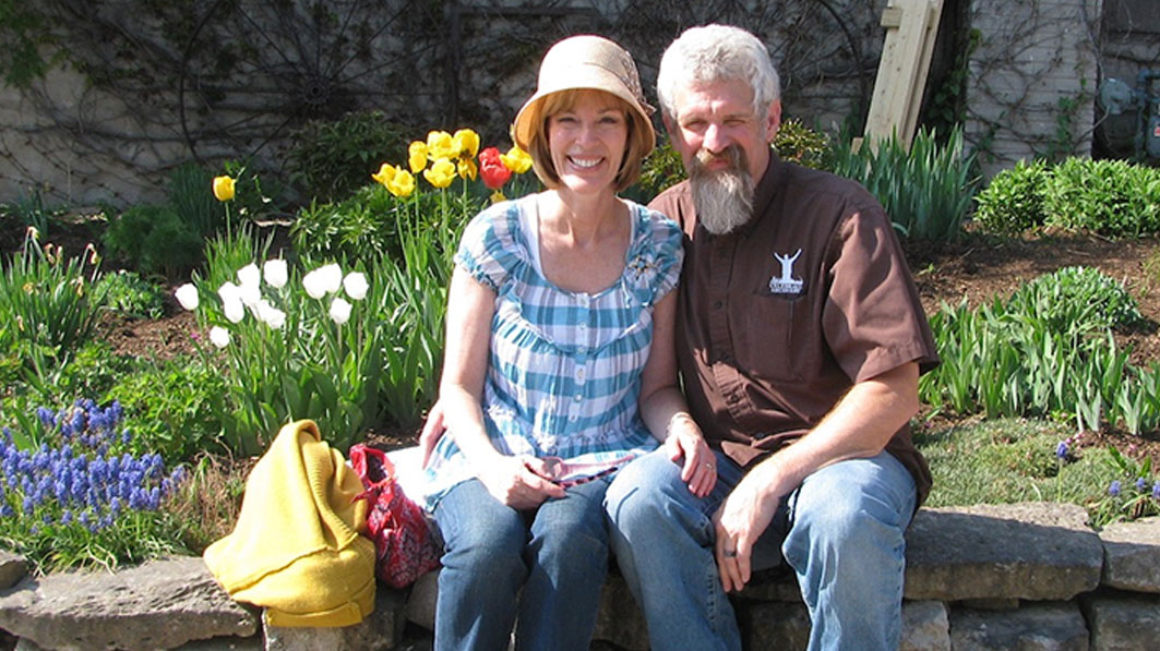 Mac and Mary Owen sitting together on a ledge in front of a flower garden