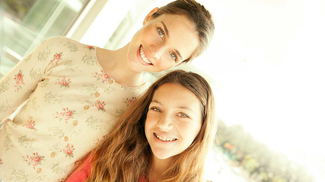 Smiling mom and teen daughter standing together, posing for the camera